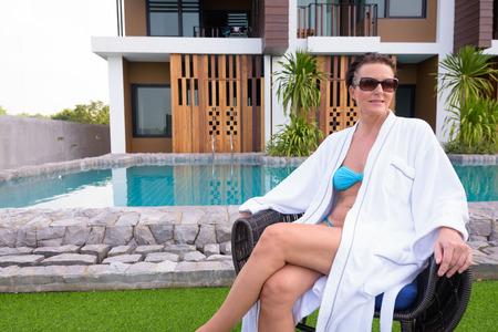 Mature beautiful Scandinavian tourist woman sitting near swimming pool in resort Stock Photo
