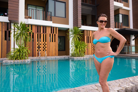 Mature beautiful Scandinavian tourist woman in bikini standing next to swimming pool Stock fotó