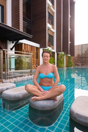 Mature tourist woman doing yoga and meditation next to swimming pool