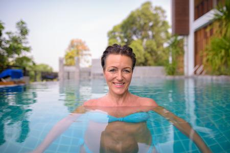 Mature beautiful Scandinavian tourist woman in swimming pool