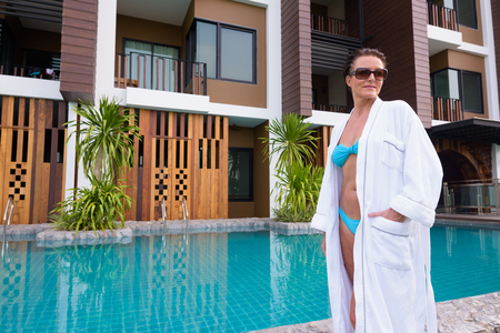Mature beautiful Scandinavian tourist woman standing next to swimming pool Stock Photo
