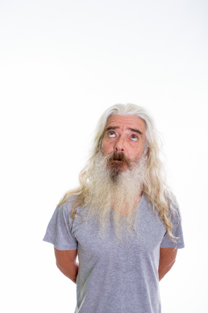 Studio shot of senior bearded man thinking while looking up with