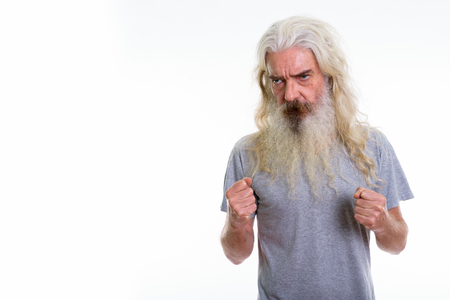Studio shot of senior bearded man looking angry