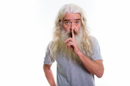 Studio shot of senior bearded man with finger on lips