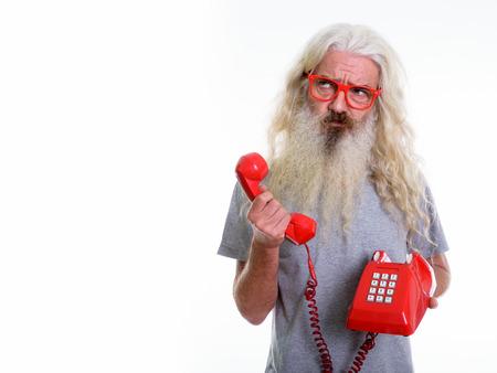 Studio shot of senior bearded man holding old telephone while th