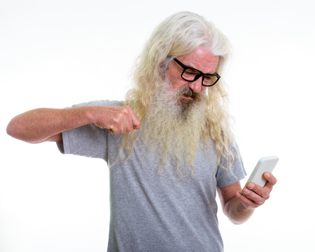 Studio shot of angry senior bearded man using mobile phone and r
