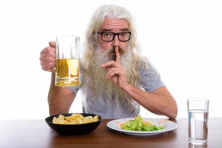 Studio shot of senior bearded man holding glass of beer while sh