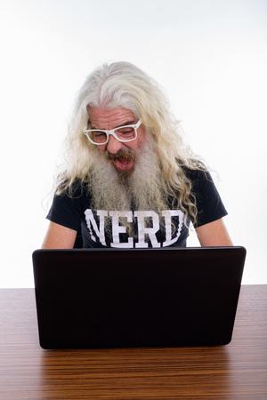 Studio shot of senior bearded nerd man looking shocked while usi
