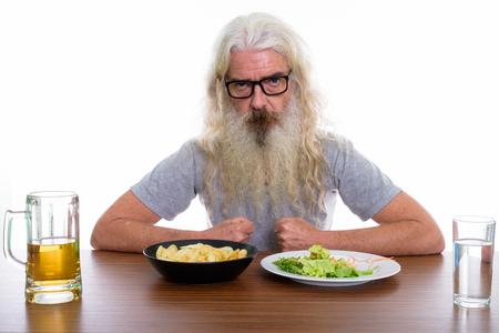 Studio shot of senior bearded man wearing eyeglasses with health