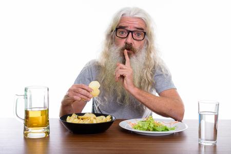 Studio shot of senior bearded man holding potato chips while shu Stock Photo