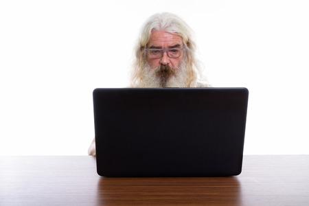 Studio shot of senior bearded man wearing eyeglasses while using Banque d'images