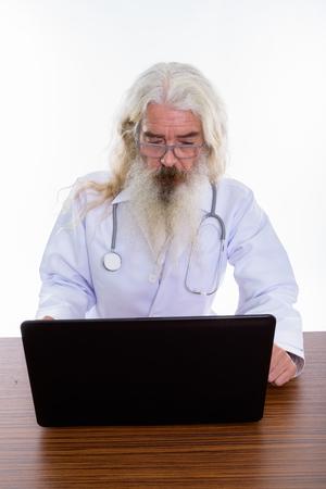 Studio shot of senior bearded man doctor using laptop on wooden