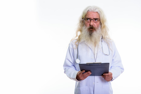 Studio shot of senior bearded man doctor thinking while holding Banque d'images