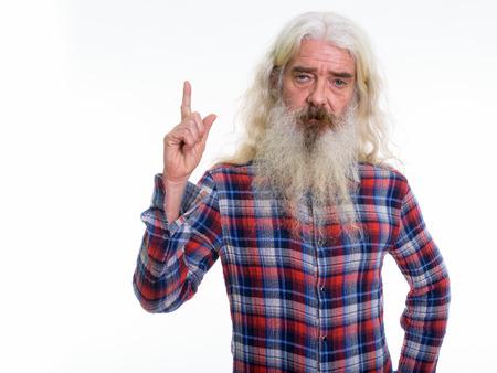 Studio shot of senior bearded man pointing finger up