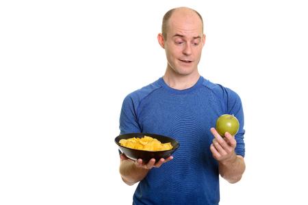 Bald Caucasian man  choosing between bowl of potato chips and gr