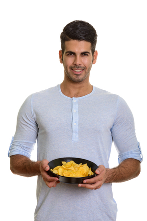 Young happy Persian man smiling and holding bowl of potato chips