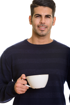 Young happy Persian man smiling and holding coffee cup Stock Photo