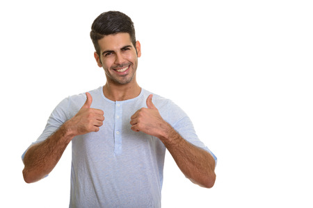 Young happy Persian man smiling giving thumbs up