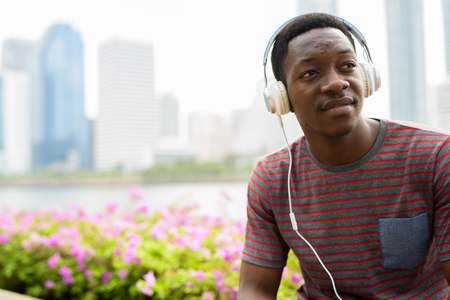 Young handsome African man sitting at park while listening music with headphones