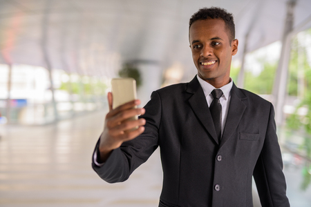 Happy successful young African businessman using mobile phone outdoors 免版税图像