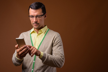 Portrait of handsome man using mobile phone against brown background Stok Fotoğraf