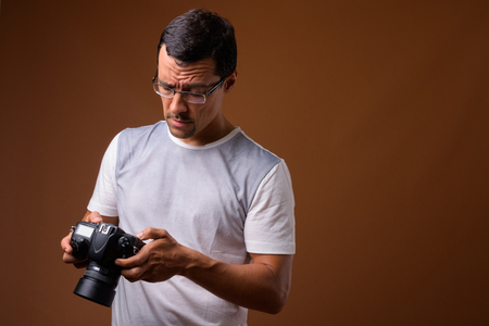 Portrait of photographer man against brown background 版權商用圖片