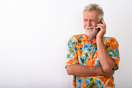 Studio shot of senior bearded tourist man looking stressed while