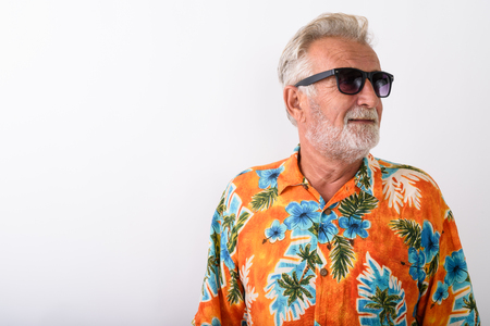 Studio shot of happy senior bearded tourist man smiling while th