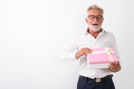 Studio shot of happy senior bearded man smiling while opening gi