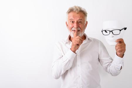 Studio shot of happy senior bearded man smiling with finger on l