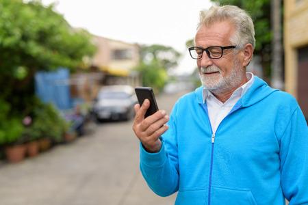 Primo piano di un bell'uomo barbuto anziano felice che sorride mentre si usa