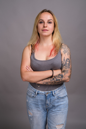 Junge schöne Frau mit blonden Haaren vor grauem Hintergrund Standard-Bild