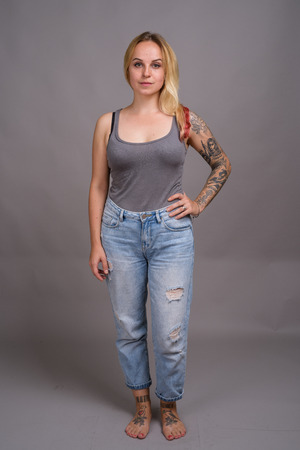 Young beautiful woman with blond hair against gray background Foto de archivo