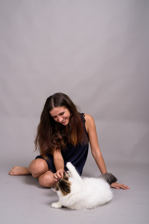 Portrait of young beautiful woman with cat against gray background Archivio Fotografico