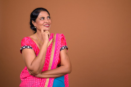 Happy Indian woman wearing Sari Indian traditional clothes and thinking Stock Photo