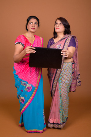 Two mature Indian women holding laptop computer while thinking