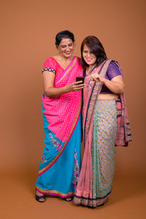 Two mature Indian women using mobile phone together Stock Photo