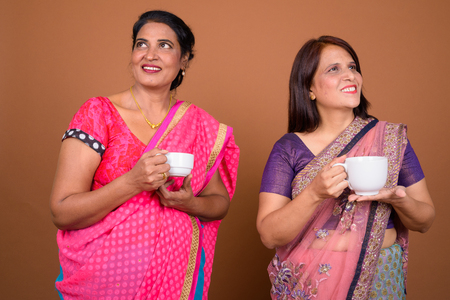 Two mature Indian women holding coffee or tea cup Stock Photo