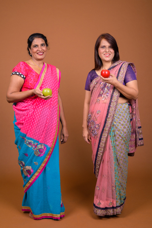 Two mature Indian women holding healthy apple in their hand