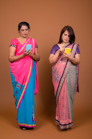 Two mature Indian women using mobile phone Stock Photo