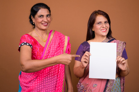Two Indian woman holding empty white paper with copy space