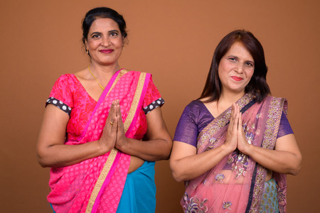Two Indian woman wearing traditional clothes greeting Stock Photo