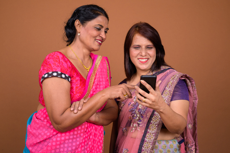 Two happy mature Indian woman using mobile phone together