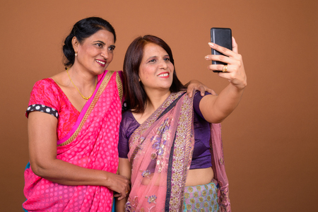 Two happy Indian woman taking selfie with mobile phone