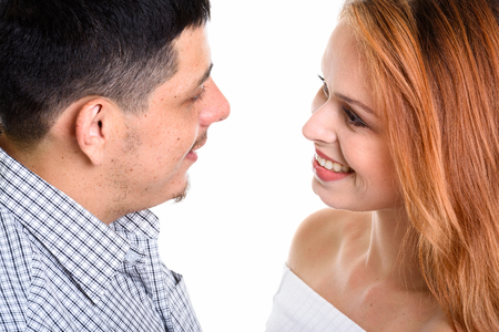 Young Hispanic couple smiling and looking at each other in love