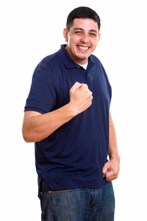 Studio shot of young happy Hispanic man smiling while looking mo