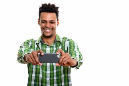 Studio shot of young happy African man smiling while taking pict Banco de Imagens