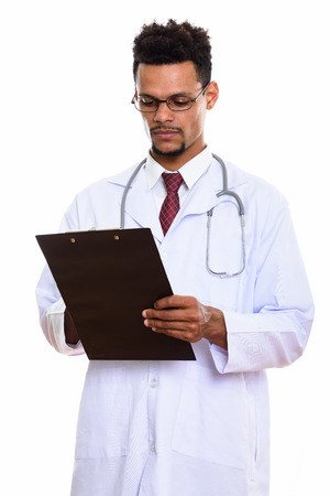 Studio shot of young African man doctor reading on clipboard