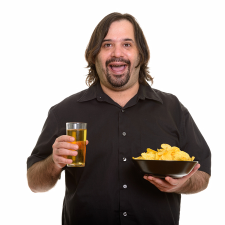 Happy fat bearded Caucasian man smiling while holding bowl of ch
