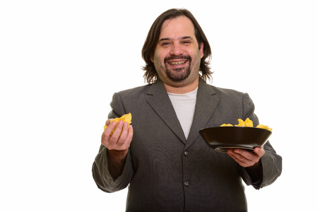 Happy fat Caucasian businessman smiling and holding mouthful of Stock Photo